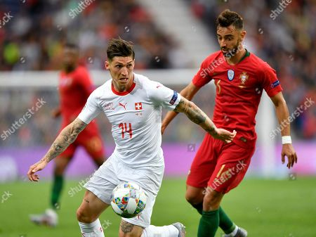 Switzerland's Steven Zuber, left, and Portugal's Bruno Fernandes, right, challenge for the ball during the UEFA Nations League semifinal soccer match between Portugal and Switzerland at the Dragao stadium in Porto, Portugal