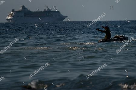 A man fishes in the sea on a makeshift raft while the Empress of the Seas, a Royal Caribbean vessel, leaves the harbor in Havana, Cuba, . Major cruise lines on Wednesday immediately began dropping stops in Cuba from their itineraries and hastily rerouting ships to other destinations including Mexico, after the Trump administration's new restrictions on travel to Cuba