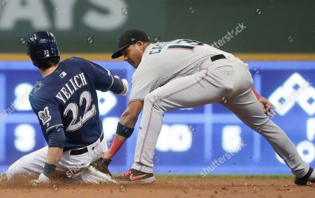 Miami Marlins' Starlin Castro tags out Milwaukee Brewers' Christian Yelich at second as Yelich tried stretching a single into a double during the first inning of a baseball game, in Milwaukee