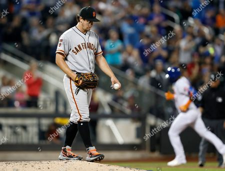 Derek Holland, Adeiny Hechavarria. San Francisco Giants relief pitcher Derek Holland stands on the mound after allowing a solo home run to New York Mets Adeiny Hechavarria during the seventh inning of a baseball game, in New York