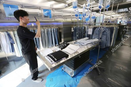 Customer Kim Kun Woo uses his smartphone to take photos at an unmanned jeans shop in Seoul, South Korea. The 24/7 denim shop lets customers try on jeans and pay using a self-service digital system without having to deal with sales staff, though sometimes technical glitches can pose a problem