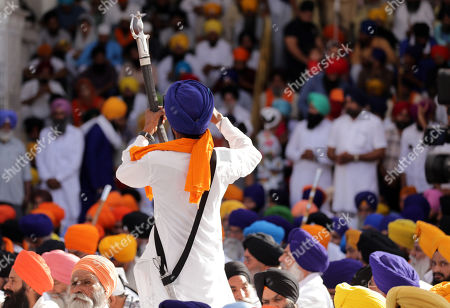 Stock Image of A Sikh man holds his ceremonial sword as he makes video clips as Sikhs gather in large numbers to attend a memorial for the hundreds of people who were killed during Operation Blue Star in 1984, at the Akaal Takhat, the highest temporal seat for the Sikhs, within the Golden Temple premises, the holiest of Sikh shrines in Amritsar, India, 06 June 2019. Sikhs are marking the 35th anniversary of Operation Blue Star, that took place from 03 to 08 June 1984, when the Indian Army stormed the Golden Temple to flush out Sikh separatists and arrest Jarnail Singh Bhindranwale, a Sikh separatist leader, and his followers who had initiated a movement to establish a separate Sikh state called Khalistan.