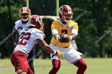Stock Photo of Dwayne Haskins, Craig Reynolds. Washington Redskins quarterback Dwayne Haskins Jr., right, hands the ball to running back Craig Reynolds (22) during an NFL football minicamp at Redskins Park in Ashburn, Va