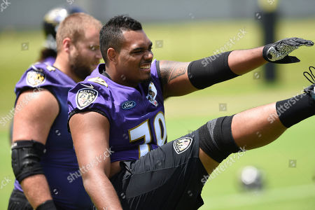 Baltimore Ravens' Ronnie Stanley warms up during an NFL football practice, in Owings Mills, Md
