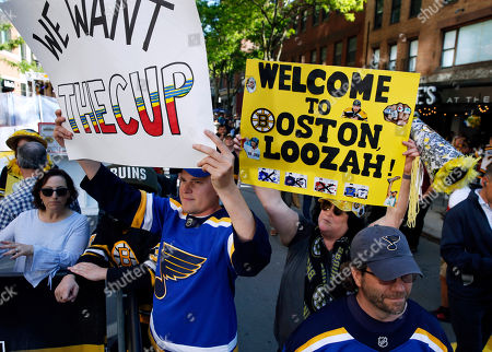 St. Louis Blues fan Brent Pearson, left, and Boston Bruins fan Lisa Ouimette hold signs supporting their teams before Game 5 of the NHL hockey Stanley Cup Final between the Blues and the Bruins, in Boston