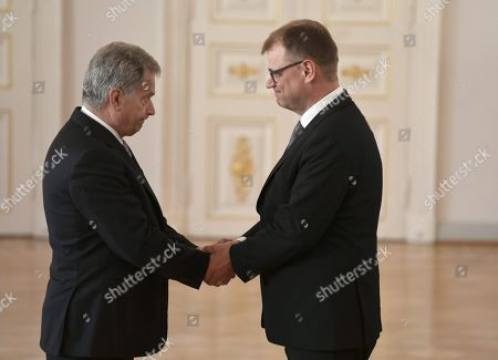 Stock Picture of Finnish President Sauli Niinisto shakes hands with outgoing Prime Minister Juha Sipila as the old government of Finland pays a complimentary farewell visit to the President of Finland at the Presidential Palace