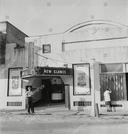 Movie theatre, the New Glades theater, with posters advertising PENNIES FROM HEAVEN, and THE SAINT IN NEW YORK, Moore Haven, Florida, photograph by Marion Post Wolcott, January, 1939.