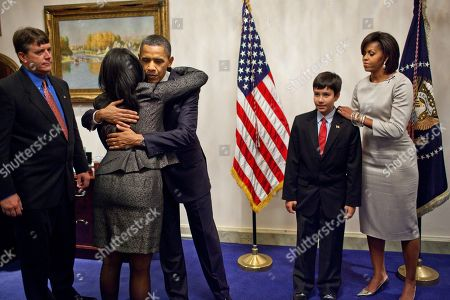 Stock Image of President and Michelle Obama greet the grieving Green family whose nine-year-old daughter Christina Taylor was killed during the assassination attempt on Rep. Gabrielle Giffords on Jan. 8 2011. Michelle wears a memorial ribbon on her silver silk shift from Rachel Roys 2012 Fall collection and Lucite bangle bracelets by Kara Ross.,