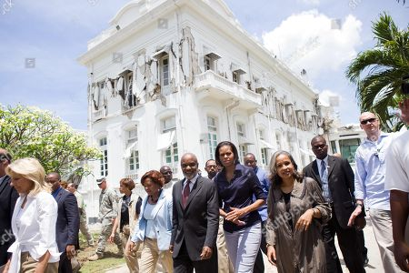 Michelle Obama and Jill Biden tour earthquake damage in Port Au-Prince Haiti with Haitian President Rene Preval and his wife Elisabeth Delatour Preval. The damaged presidential palace is in the background. April 13 2010.,