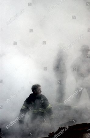 NYC Fireman emerges from the smoke and debris of the World Trade Center on Sept. 14, 2001. New York City, after September 11, 2001 terrorist attacks. U.S. Navy Photo by Jim Watson