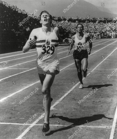 Roger Bannister leads John Landy of Australia across the finish line at British Empire Games, 1954. It was the first mile race in history in which two runners finished under four minutes. Vancouver, B.C.