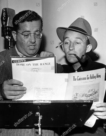 Orchestra leader JOHN SCOTT TROTTER and BING CROSBY go over lyrics for Home on the Range and The Caissons Go Rolling Along - requested by General MacArthur for broadcast to the Philippines, 1/29/42