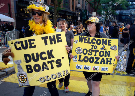 Boston Bruins fans Maryellen Cahill, left, and Lisa Ouimette carry signs supporting their team before Game 5 of the NHL hockey Stanley Cup Final between the Bruins and the St. Louis Blues, in Boston