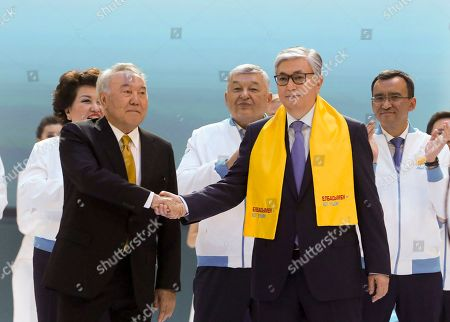 Kazakhstan's acting President Kassym-Jomart Tokayev, right, and Former Kazakh President Nursultan Nazarbayev shake hands in front of their supporters in Nur-Sultan, the capital city of Kazakhstan, . For the first time in nearly three decades of independence, Kazakhstan is holding a presidential election without Nursultan Nazarbayev on the ballot. But the longtime leader of the oil-rich Central Asian country still casts a long shadow on the vote