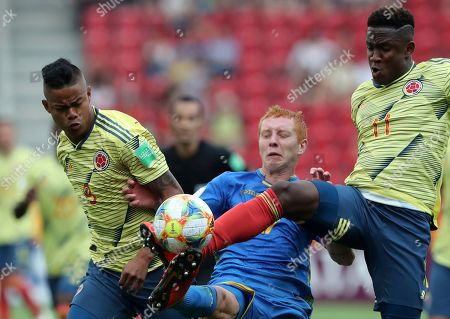 Ukraine's Yukhym Konoplia, center, duels for the ball with Colombia's Luis Sandoval, left, and Colombia's Luis Sinisterra during the quarter final match between Colombia and Ukraine at the U20 World Cup soccer in Lodz, Poland