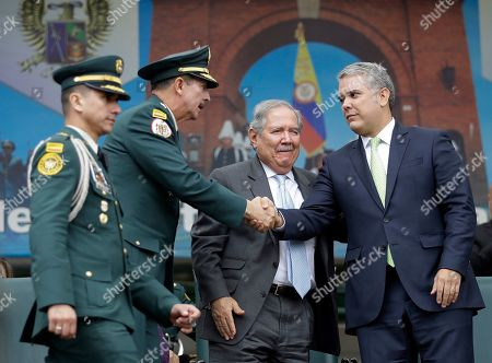 The president of Colombia, Ivan Duque, right, shakes hands with army commander, General Nicacio Martínez Espinel, left, as Colombia's Defense Minister Guillermo Botero, center, smiles during a military ceremony in Bogotá, Colombia, . General Martínez was promoted to a fourth star amid an outcry over an order he issued that has stirred fears of a return to serious human rights violations