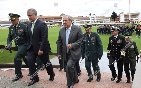Ivan Duque, Guillermo Botero. Colombia's President Ivan Duque, second left, and Defense Minister Guillermo Botero, center, accompanied by their military and police commanders attend a military ceremony in Bogotá, Colombia