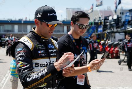 Aric Almirola signs autographs after a practice session for the NASCAR cup series race at Michigan International Speedway, in Brooklyn, Mich