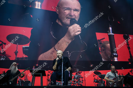 Phil Collins (C) performs on stage next to bassist Leland Sklar (L) and guitarist Daryl Stuermer (R) during a concert in Berlin, Germany, 07 June 2019, as part of his 'Not Dead Yet' tour.
