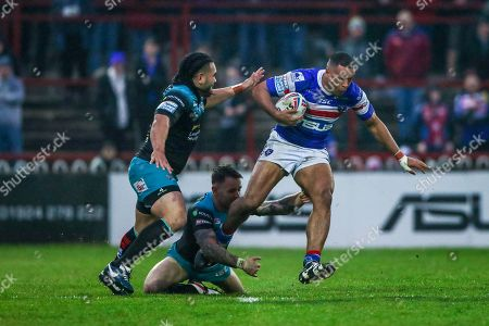 Wakefield's Reece Lyne escapes the tackle of Leeds' Richie Myler and Konrad Hurrell.