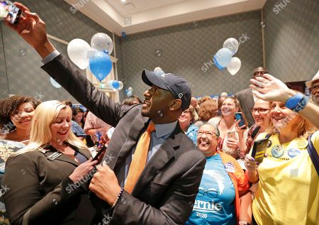 Former Florida Democratic gubernatorial nominee Andrew Gillum, center, takes a photo with supporters during a gathering at the Florida Democratic Party state conference, in Orlando, Fla