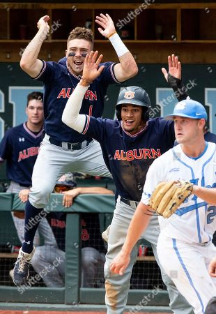 Auburn's Judd Ward (1) and Will Holland, center, celebrate behind North Carolina's Hansen Butler (24) as Auburn takes the lead over North Carolina during Game 1 at the NCAA college baseball super regional tournament in Chapel Hill, N.C