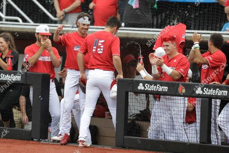 Louisville's Bobby Miller (15) is greeted by teammates after being taken out of the game during the ninth inning in Game 2 of an NCAA college baseball super regional tournament against East Carolina, in Louisville, Ky. Louisville won 12-0