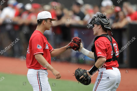 Louisville's Bobby Miller, left, is greeted by Henry Davis during the eighth inning in Game 2 of an NCAA college baseball super regional tournament against East Carolina, in Louisville, Ky. Louisville won 12-0