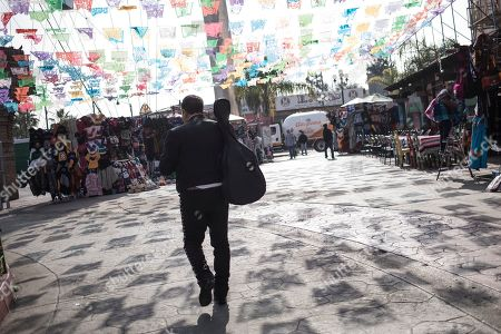 "A musician walks near the plaza where Mexican President Andres Manuel Lopez Obrador will hold a rally, in Tijuana, Mexico, . Mexican President Andres Lopez Obrador is to hold a rally in Tijuana even as President Trump has put on hold his plan to begin imposing tariffs on Mexico on Monday, saying the U.S. ally will take ""strong measures"" to reduce the flow of Central American migrants into the United States"