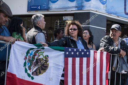 "Stock Photo of Lilia Lara, a Tijuana resident, displays the U.S. and Mexican flags at the plaza where Mexican President Andres Lopez Obrador is to hold a rally in Tijuana, Mexico, . President Trump has put on hold his plan to begin imposing tariffs on Mexico on Monday, saying the U.S. ally will take ""strong measures"" to reduce the flow of Central American migrants into the United States. Lara said she arrived early to get a good spot for the rally"