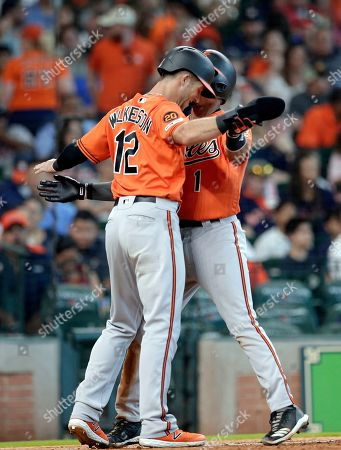 Baltimore Orioles' Stevie Wilkerson (12) and Richie Martin (1) celebrate at the plate after they scored on a two-un home run by Martin during the ninth inning of a baseball game against the Houston Astros, in Houston