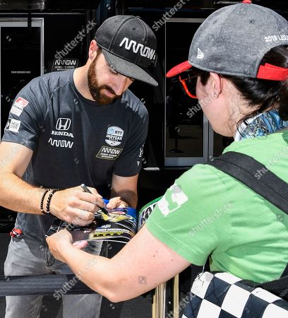 IndyCar driver James Hinchcliffe autographs memorabilia for a fan before a IndyCar auto race at Texas Motor Speedway, in Fort Worth, Texas