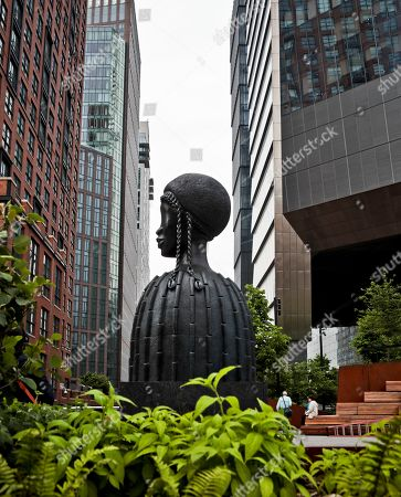 """Stock Image of A bronze bust of a Black woman entitled """"Brick House,"""" by Chicago artist Simone Leigh, is seen among the buildings and vegetation in the High Line park section called """"The Spur,"""" located at West 30th Street and 10th Avenue. Once a land of industrial buildings, parking lots and auto repair businesses, the neighborhood around the High Line is now anchored at one end by the dazzling new home of the Whitney Museum of American Art and and at the other by Hudson Yards, a $25 billion development of skyscrapers, shops and a performing arts center"""