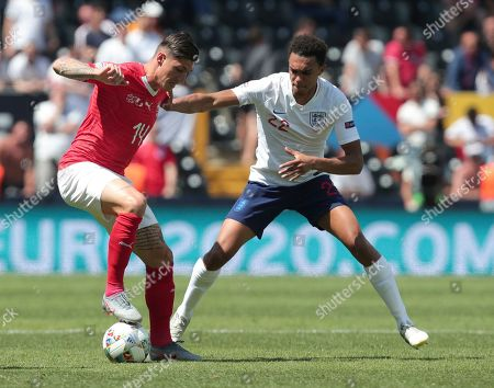 Switzerland's Steven Zuber, left, and England's Trent Alexander-Arnold challenge for the ball during the UEFA Nations League third place soccer match between Switzerland and England at the D. Afonso Henriques stadium in Guimaraes, Portugal