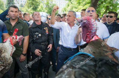 Vladimir Plahotniuc, the leader of the Moldova's Democratic party, and the country's de facto leader, clenches his fist gesturing next to interim president Pavel Filip, right, as people hold turkeys before throwing them over the fence of the Modovan presidency building in Chisinau, Moldova, . Moldova's interim president Pavel Filip has dissolved parliament and called for snap elections on Sept. 6 amid a months-long political crisis, announcing his decision shortly after his appointment on Sunday by the Constitutional Court to replace president Igor Dodon