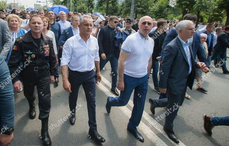 Vladimir Plahotniuc, center left, the leader of the Moldova's Democratic party, and the country's de facto leader, walks with interim president Pavel Filip, center right, during a protest in Chisinau, Moldova, . Moldova's interim president Pavel Filip has dissolved parliament and called for snap elections on Sept. 6 amid a months-long political crisis, announcing his decision shortly after his appointment on Sunday by the Constitutional Court