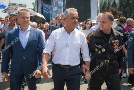 Vladimir Plahotniuc, center, the leader of the Moldova's Democratic party, and the country's de facto leader, walks during a protest in Chisinau, Moldova, . Moldova's interim president Pavel Filip has dissolved parliament and called for snap elections on Sept. 6 amid a months-long political crisis, announcing his decision shortly after his appointment on Sunday by the Constitutional Court