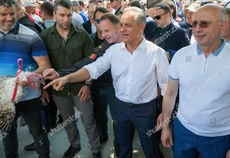 Vladimir Plahotniuc, the leader of the Moldova's Democratic party, and the country's de facto leader, points his hand next to interim president Pavel Filip, right, as people hold turkeys before throwing them over the fence of the Modovan presidency building in Chisinau, Moldova, . Moldova's interim president Pavel Filip has dissolved parliament and called for snap elections on Sept. 6 amid a months-long political crisis, announcing his decision shortly after his appointment on Sunday by the Constitutional Court