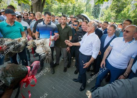 Vladimir Plahotniuc, the leader of the Moldova's Democratic party, and the country's de facto leader, gestures next to interim president Pavel Filip, right, as people hold turkeys before throwing them over the fence of the Modovan presidency building in Chisinau, Moldova, . Moldova's interim president Pavel Filip has dissolved parliament and called for snap elections on Sept. 6, announcing his decision shortly after his appointment on Sunday by the Constitutional Court