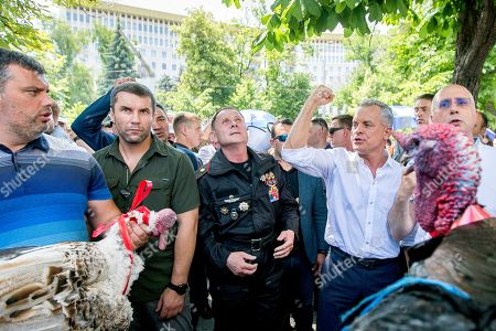 Stock Image of The leader of the Democratic Party of Moldova Vladimir Plahotniuc (2-R) gestures next to supporters holding turkeys, before his supporters will throw them over the fence of presidential building, as a sign of contempt and dishonor of the President, in Chisinau, Moldova, 09 June 2019. After forming the majority on 08 June, the parliament voted the Socialist Zinaida Grecianii as Speaker and Maia Sandu as Prime Minister. The Democratic Party tries to mentain her position and power in old government, and uses the Constitutional Court to block all decision of new Government.