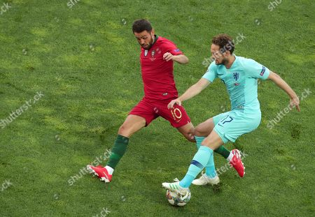 Portugal's Bernardo Silva, left, duels for the ball with Netherlands' Daley Blind during the UEFA Nations League final soccer match between Portugal and Netherlands at the Dragao stadium in Porto, Portugal