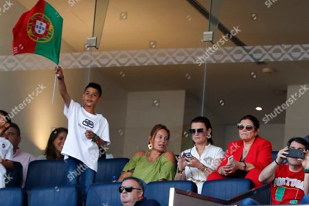 Cristiano junior, left, son of Portugal's Cristiano Ronaldo waves a flag from the stands ahead of the UEFA Nations League final soccer match between Portugal and Netherlands at the Dragao stadium in Porto, Portugal