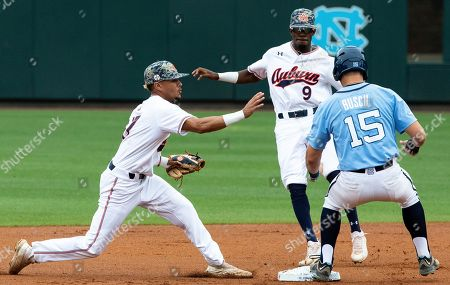 North Carolina's Michael Busch (15) safely returns to second base ahead of Auburn's Ryan Bliss (9) and Will Holland, left, during an NCAA super-regional baseball game in Chapel Hill, N.C