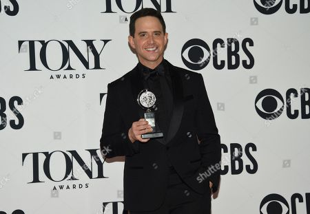 """Santino Fontana poses in the press room with the award for best performance by an actor in a leading role in a musical for """"Tootsie"""" at the 73rd annual Tony Awards, in New York"""