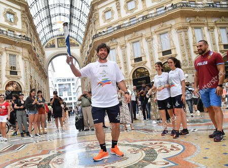 Former AC Milan player, Demetrio Albertini, stands with the torch in the Vittorio Emanuele Gallery during the third stage of the torch relay route of the 30th Summer Universiade Napoli 2019 in front of the cathedral in Milan, Italy, 10 June 2019. The 30th Summer Universiade will be held in Naples from 3 to 14 July.