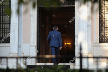 Greek Prime Minister Alexis Tsipras, enters his office after his meeting with Greek President Karolos Papoulias, in Athens, on . Tsipras visited Greece's president to formally call for the dissolution of parliament and early elections on July 7, following his party's heavy defeat in European elections last month