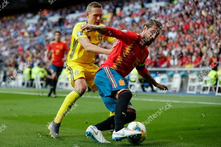 Stock Picture of Sweden's Ludwig Augustinsson, left and Spain's Sergio Ramos challenges for the ball during the Euro 2020 Group F qualifying soccer match between Spain and Sweden at the Santiago Bernabeu stadium in Madrid