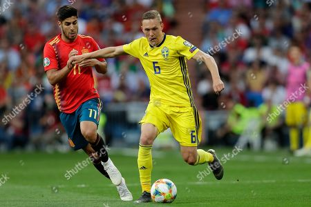 Sweden's Ludwig Augustinsson, right challenges for the ball with Spain's Marco Asensio during the Euro 2020 Group F qualifying soccer match between Spain and Sweden at the Santiago Bernabeu stadium in Madrid