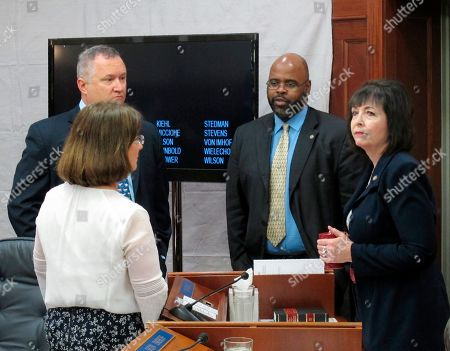 From left, Alaska state Sens. Lora Reinbold, Mike Shower, David Wilson and Shelley Hughes speak during a break in a Senate floor session, in Juneau, Alaska. The Senate on Monday approved a compromise state operating budget but failed to revive a bill that would pay residents a full dividend this year from the state's oil-wealth fund