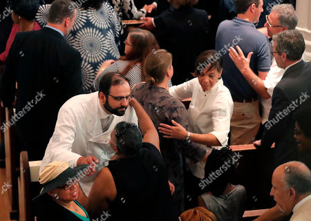 """Noted New Orleans chefs Elon Shaya, left, and Nina Compton, center facing, hug others during the sign of peace at the the funeral for Leah Chase at St. Peter Claver Church in New Orleans, . Fellow chefs, musicians, family and friends were among hundreds of admirers who filed through the church to pay last respects to Chase, the """"Queen of Creole Cuisine"""" who ran a family restaurant where civil rights strategies were discussed over gumbo and fried chicken in the 1950s and '60s"""